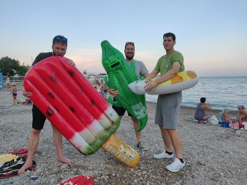 3 people fooling around with floats at the beach