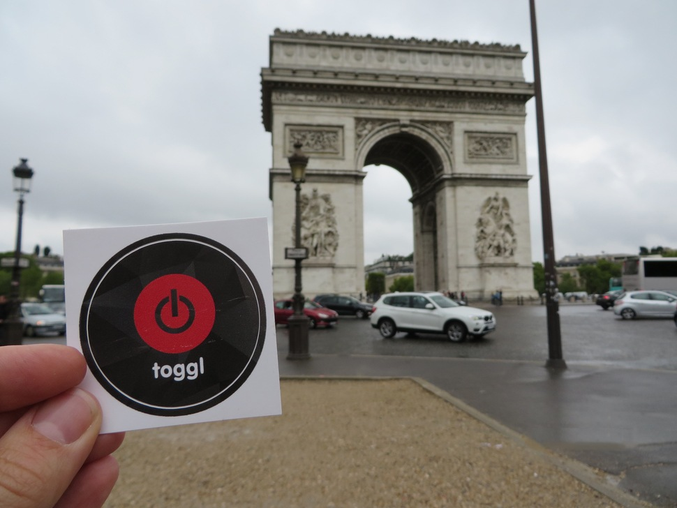 A Toggl Track sticker held in front of the Champs-Élysées