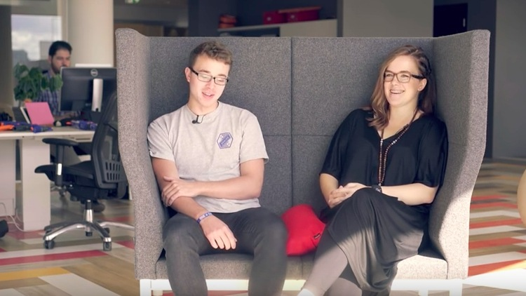 Two people sitting on a sofa smiling